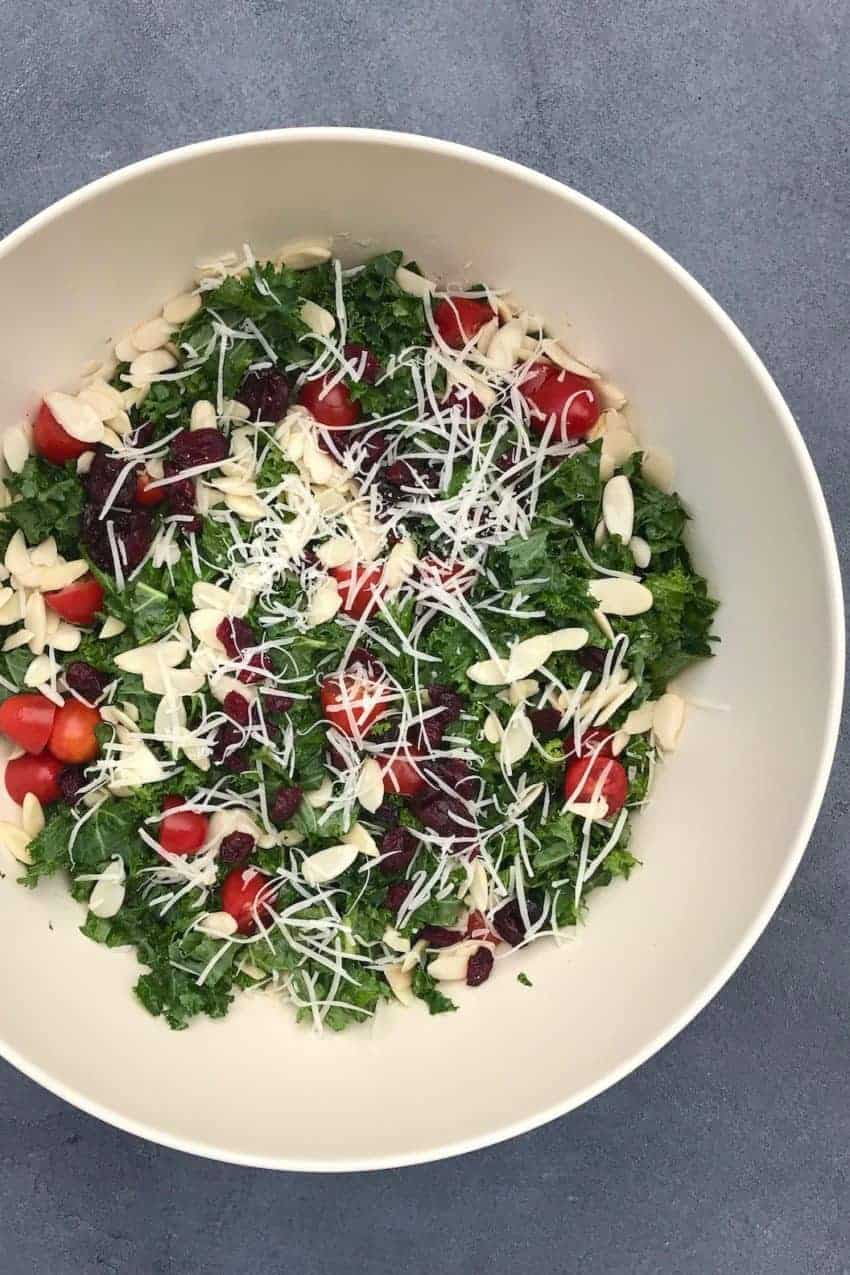 Large white bowl with kale salad, topped with sliced almonds, cranberries and shredded parmesan cheese
