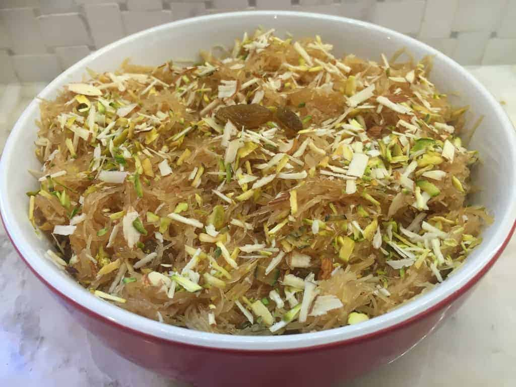 Vermicelli sheera in a bowl garnished with nuts and raisins