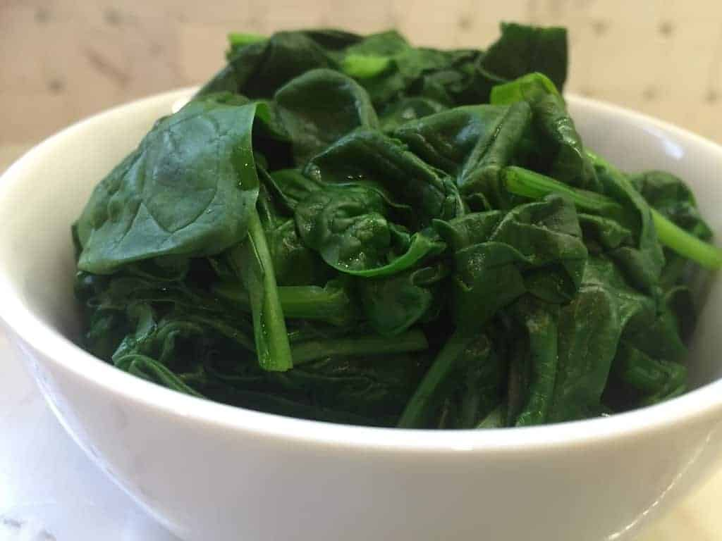 Steamed Spinach in a white bowl