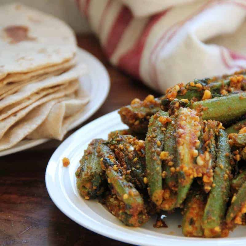 Stuffed Okra in a white platter with Indian roti's on the side in a white plate.