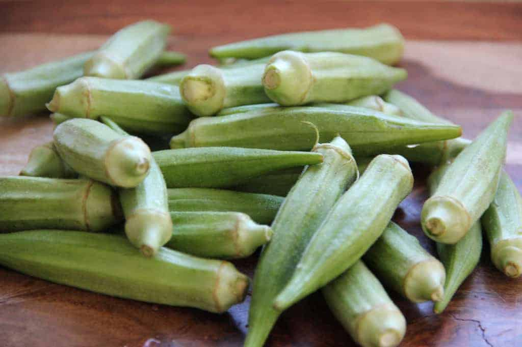 Raw okra on a wooden cutting board