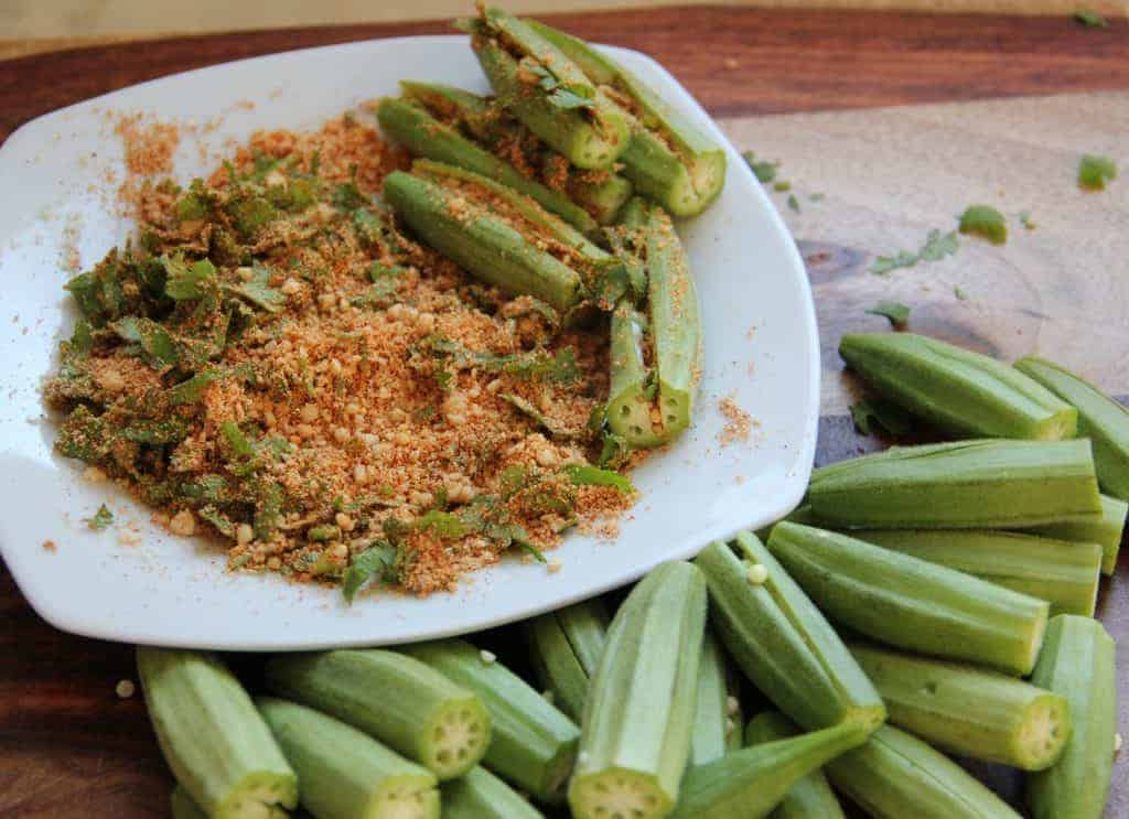 Okra being stuffed with the filling.