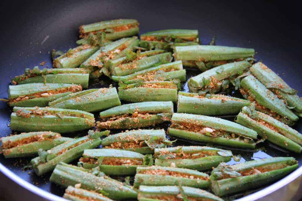 stuffed okra being fried in a pan