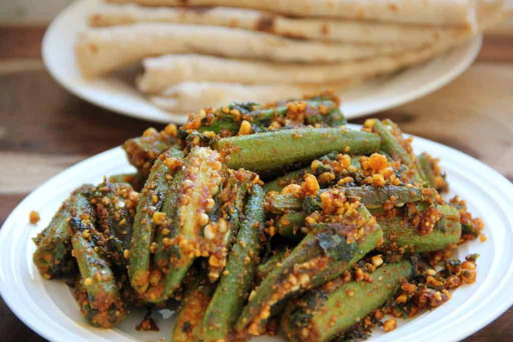 Stuffed okra served in a white platter with fresh rotis in a white plate in teh background.