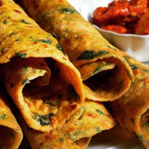 Rolled Methi Sweet Potato Parathas rolled and stacked in a plate with pickle on the side