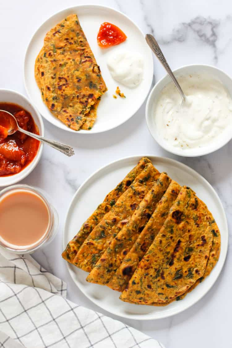 Methi Thepla in a white plate with yogurt and pickle on the side
