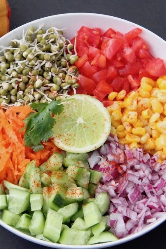 Sprouted Mung beans, diced tomatoes, corn, diced red onions, diced cucumbers, grated carrots and a lime wedge in a bowl