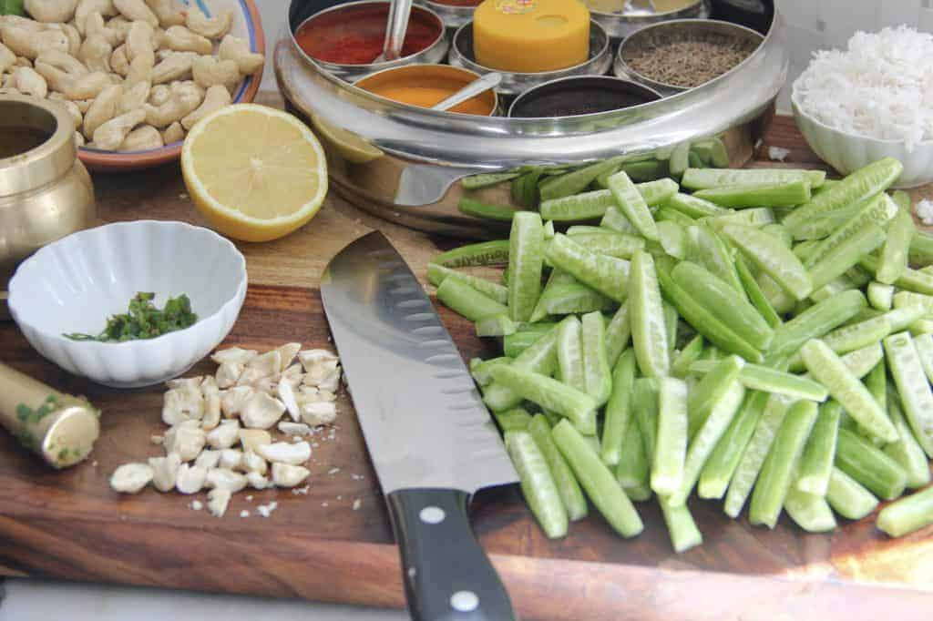 Ingredients for tindora sabzi on a wooden cutting board