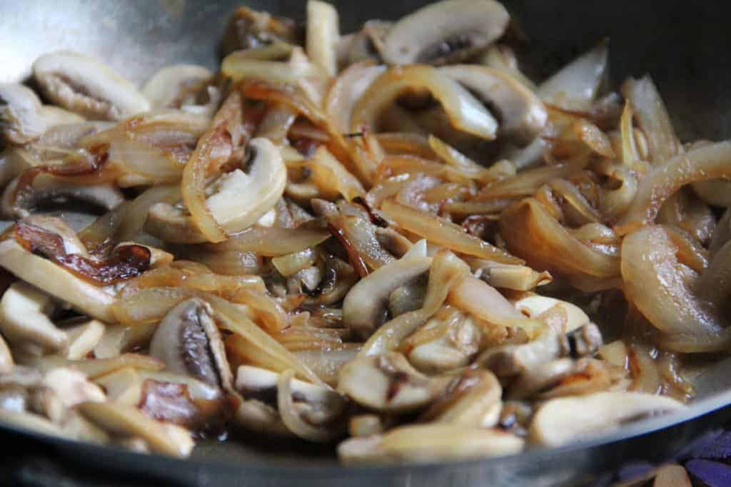 sauteed onions and mushrooms in a pan