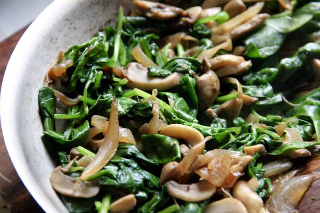 sauteed onions, mushrooms and baby spinach in a pan