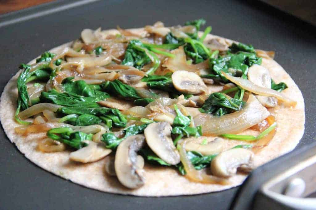 tortilla topped with spinach, onion and mushroom filling