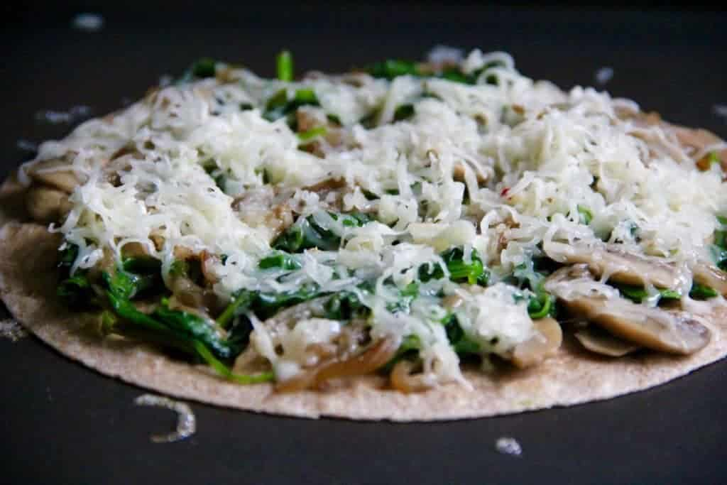 cheese topped on a tortilla over spinach and mushroom filling
