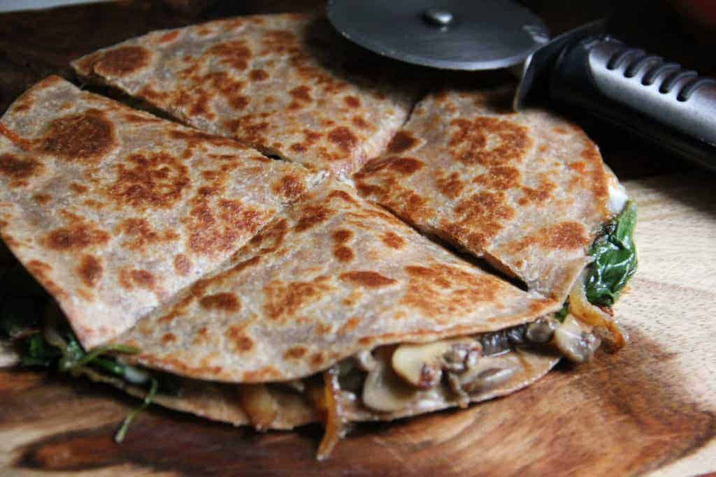 spinach and mushroom quesadilla cut into triangles
