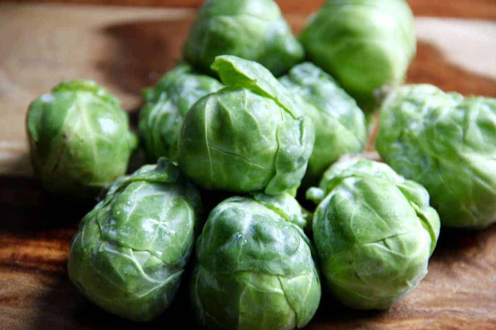 whole brussels sprouts on a wooden cutting board