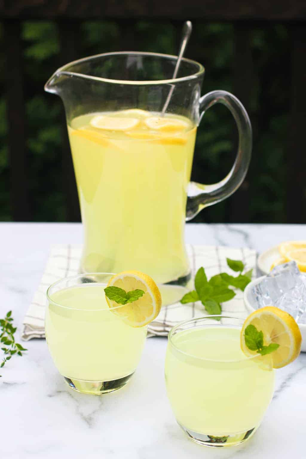 2 glasses and a large pitcher of lemonade