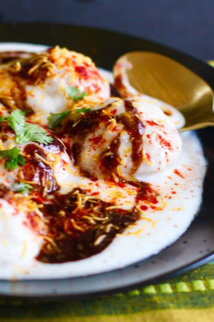 Dahivada with yogurt garnished with tamarind-date chutney, red chili powder and cilantro in a black plate