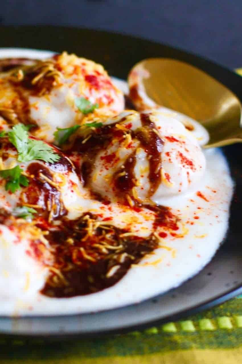Dahi Vada garnished with tamarind-date chutney, red chili powder and cilantro