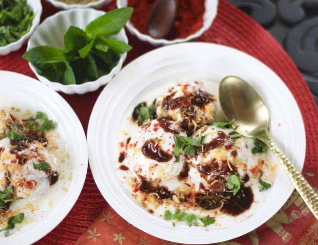 Two plates of dahi vada garnished with tamarind chutney and cilantro