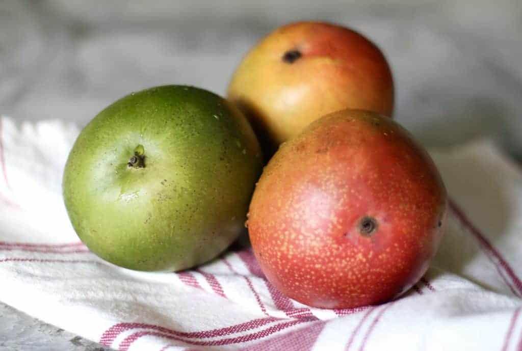 three mangoes on dish towel