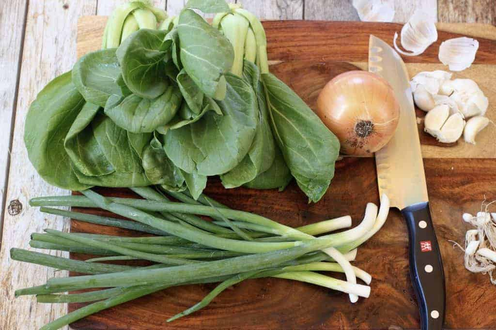 bok choy, scallions, onion and garlic on a cutting board