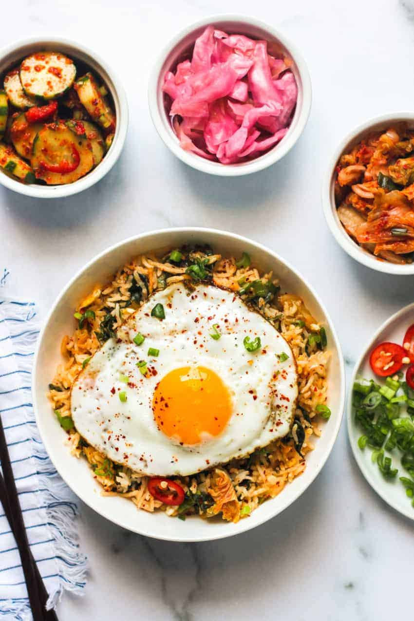 kimchi fried rice served in a white bowl with an egg on top