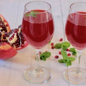 2 glasses of Pomegranate Juice with mint leaves and pomegranate arils scattered on the table