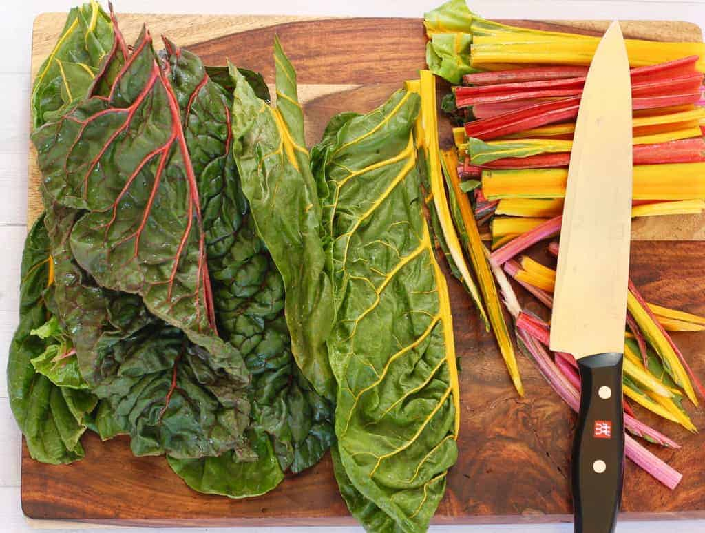Stems removed from Swiss Chard leaves on a cutting board