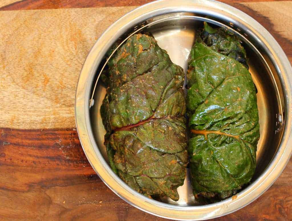 Swiss Chard leaves rolls placed in a steamer basket for Aloo Wadi
