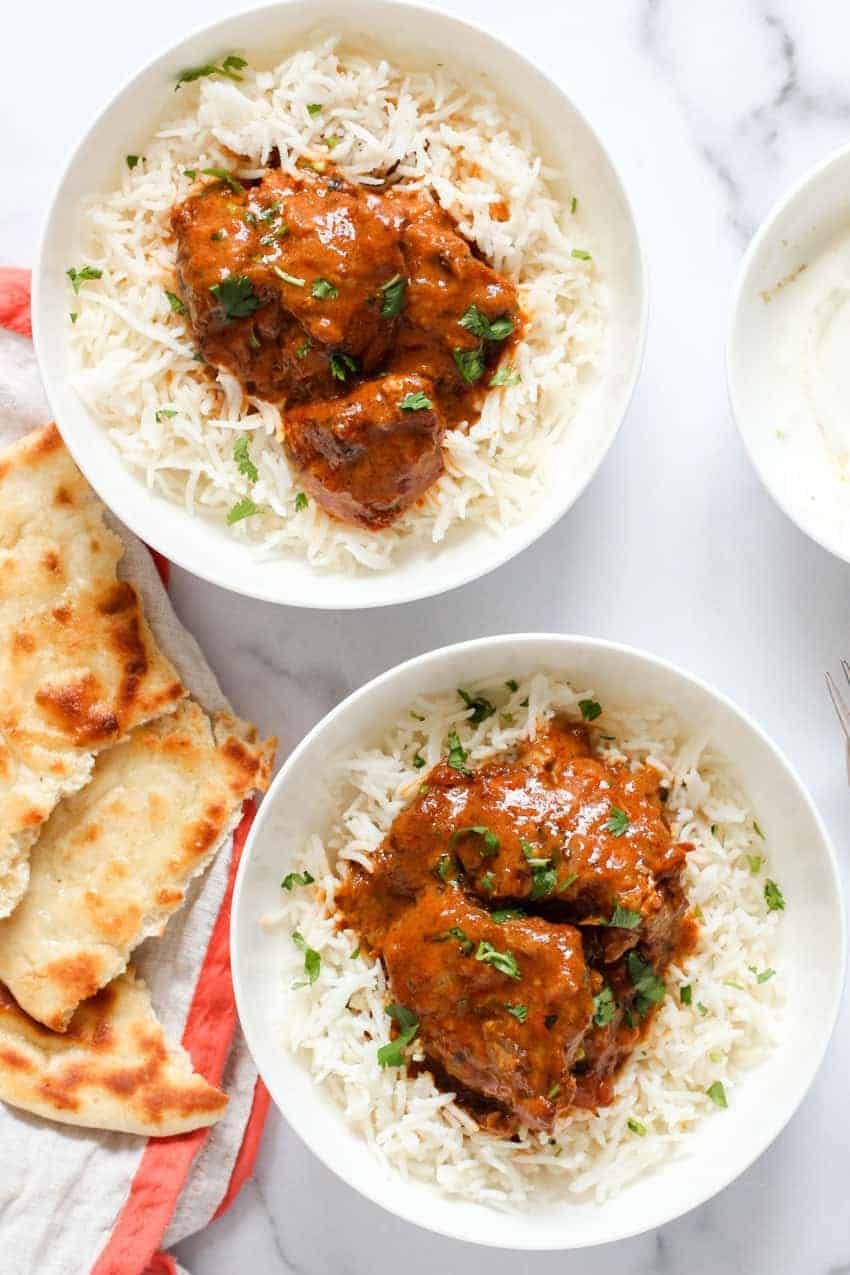 Butter Chicken Served on rice in 2 bowls and naan on the side