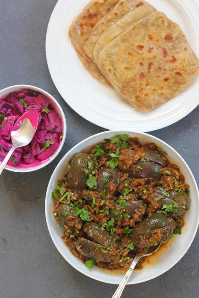 Eggplant Curry in a white bowl, parathas in a plate and a small bowl of beet raita.