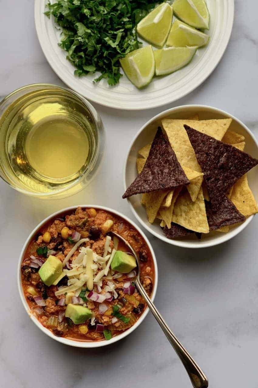 Bowl of Buffalo Chicken Chili garnished with cheese and diced avocados, with a bowl of tortilla chips, glass of drink and lime wedges in a white plate on the side
