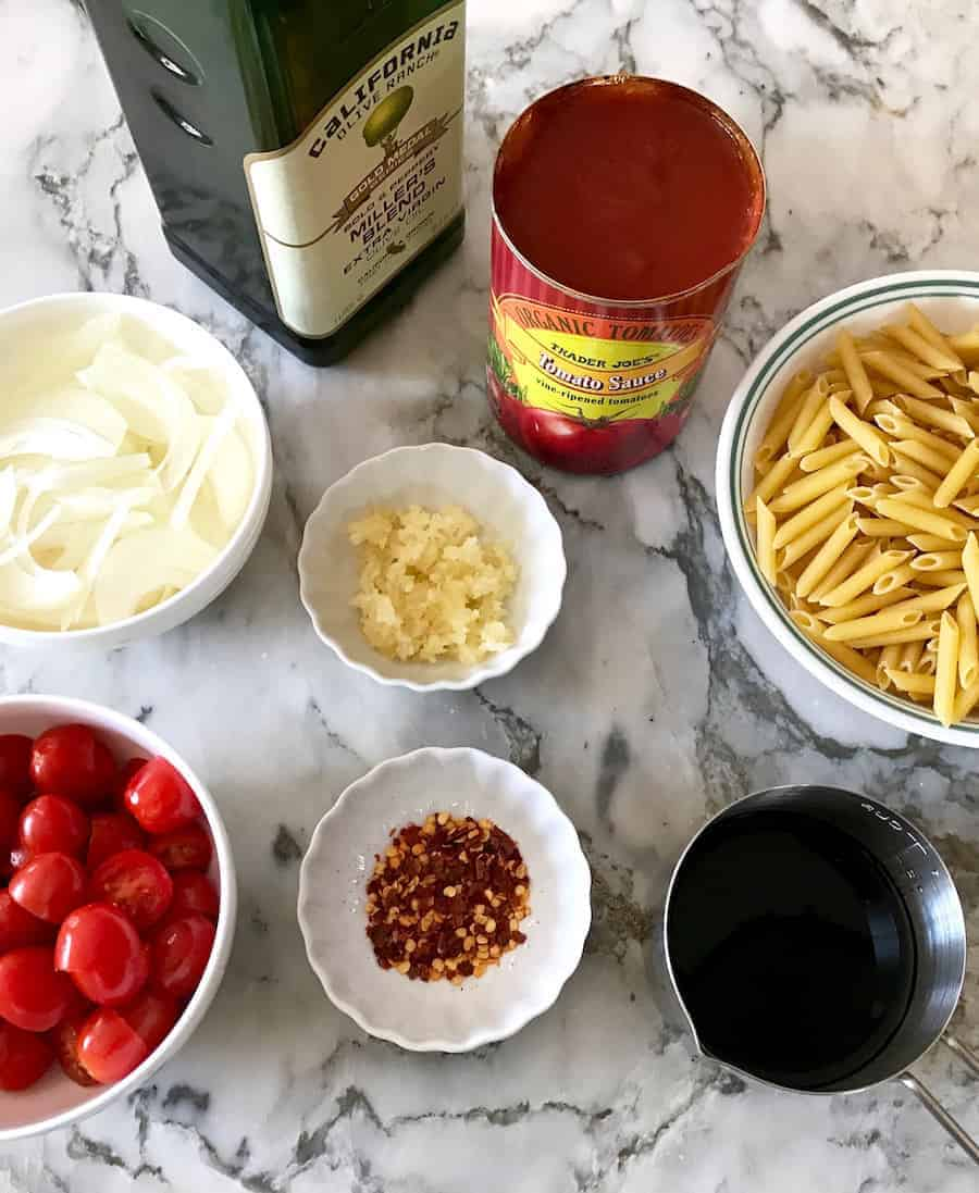 pasta caprese ingredients - olive oil, sliced onions, minced garlic, tomato sauce, sliced grape tomatoes, red chili flakes, dry pasta in a bowl and balsamic vinegar in a measuring cup.