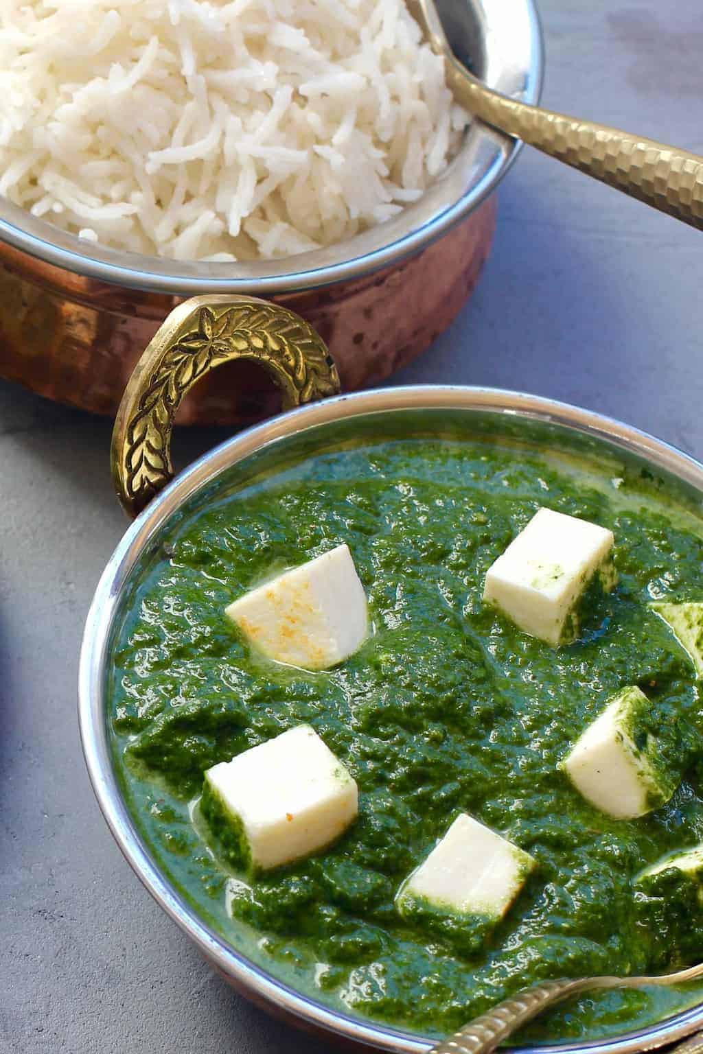 Palak Paneer in a copper bowl with rice on the side