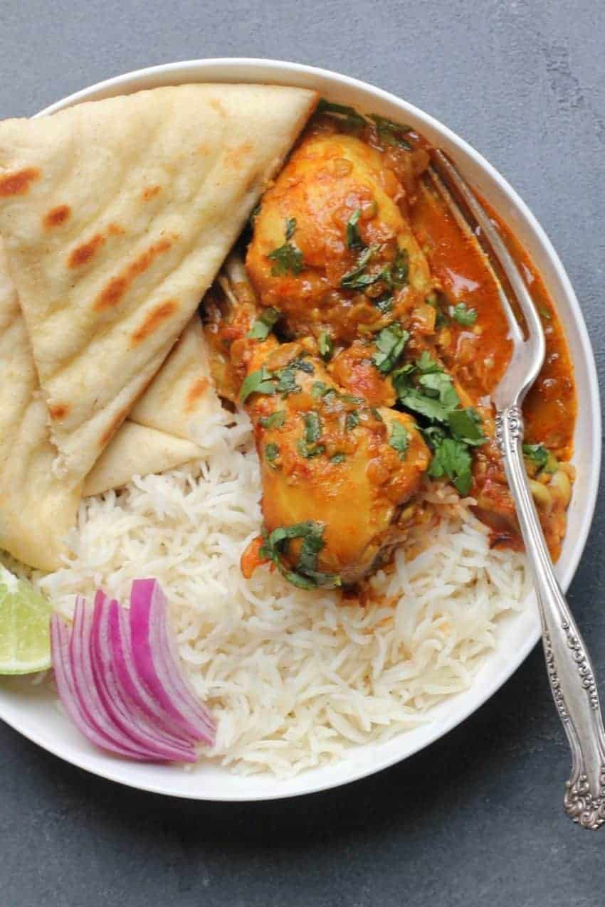 Chicken korma curry served in a white bowl with white rice and naan.