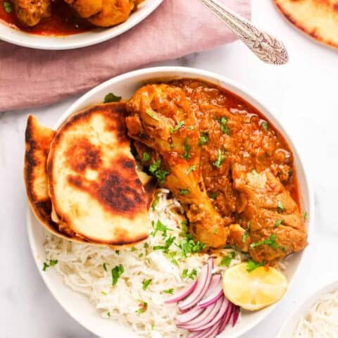 chicken korma served in a white bowl with naan and rice