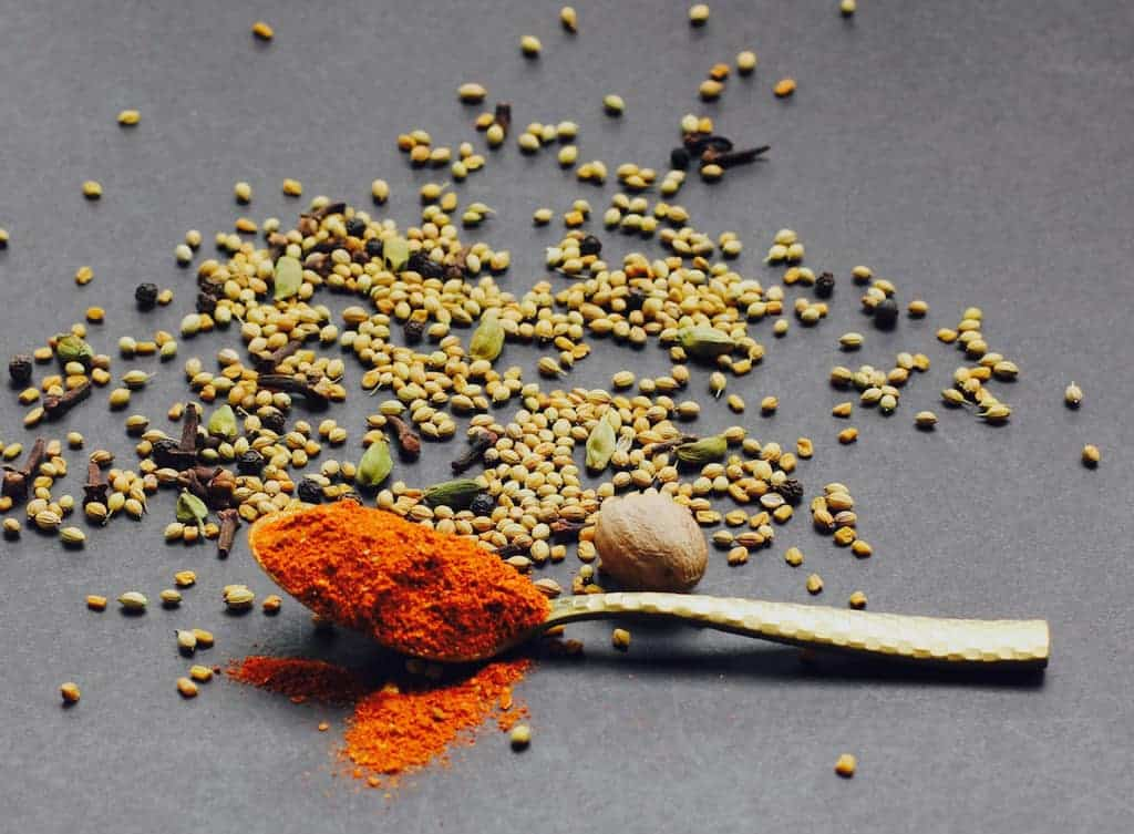 berbere spice blend in a spoon with other whole spices around