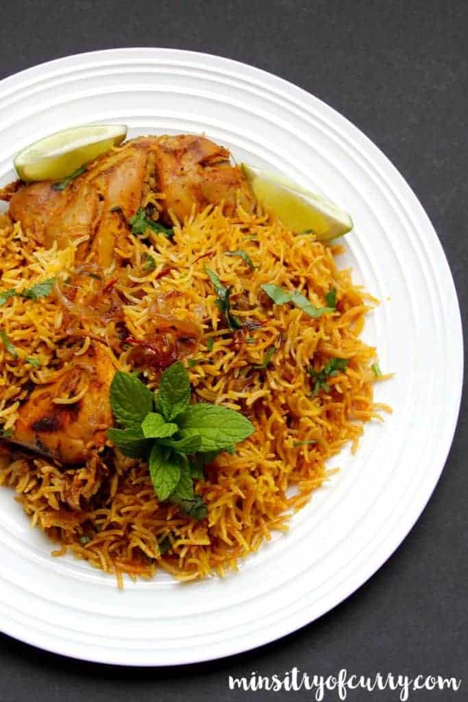 Chicken Biryani served in w white plate with mint as garnish and llime wedges on the side