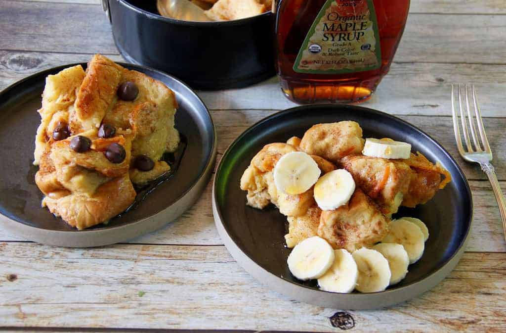 French Toast/Bread Pudding serevd in 2 plates, topped with sliced bananas and chocolate chips