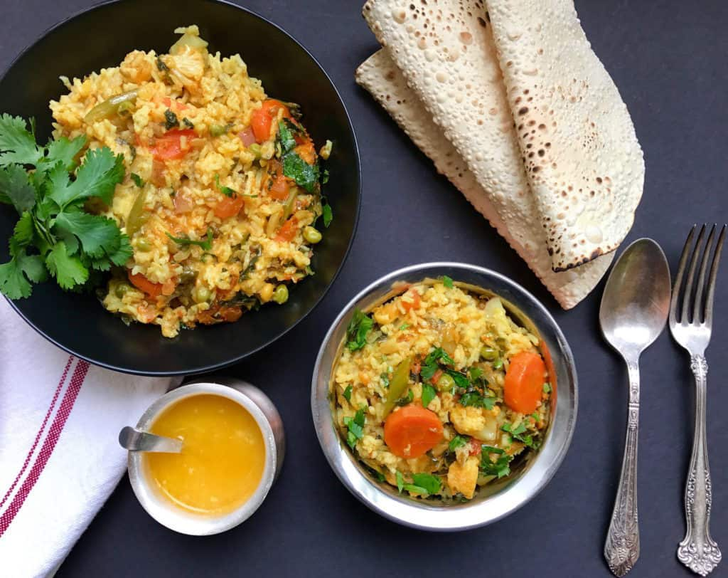 Serving bowls with mixed lentils and vegetable khichdi, bowl of ghee and roasted papadums