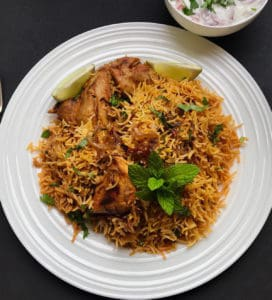 Chicken Biryani Served in a dinner plat with a bowl of raita on the side.