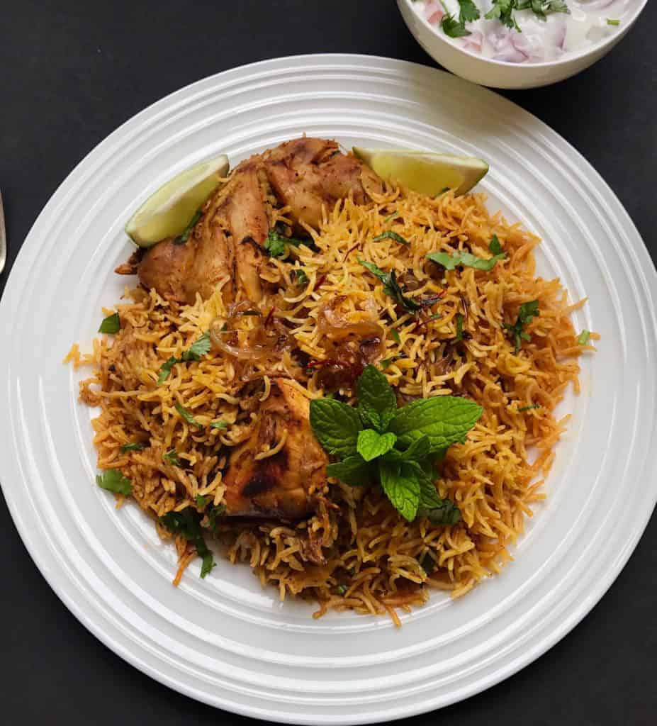 Chicken Biryani with a bowl of raita on the side.