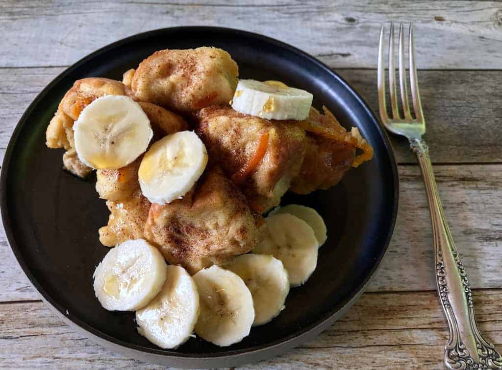 French Toast/Bread Pudding topped with sliced bananas, served in a black plate
