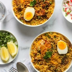 Chicken Biryani served in 2 bowls with raita and lemon wedges