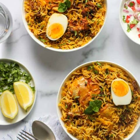 Chicken Biryani served in 2 bowls with raita and lemon wedges