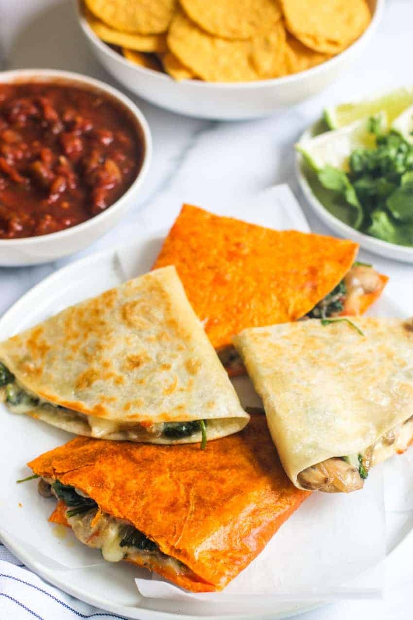 stack of spinach mushroom and onion quesadillas on a white plate