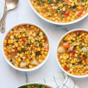 Corn Poblano chowder in 3 white bowls
