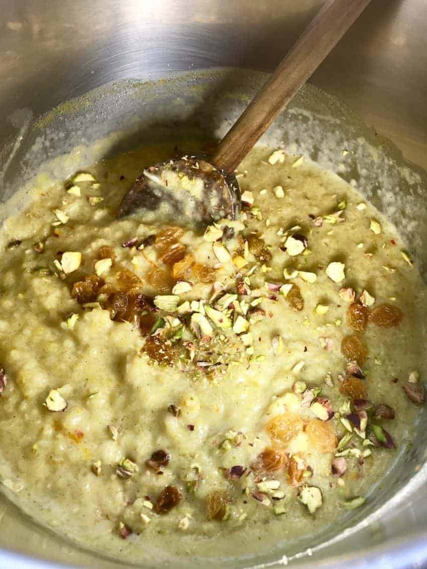 Instant Pot with Rice pudding garnished with raisins and nuts with a wooden spatula in.