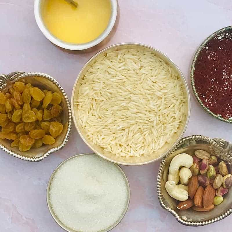 Ingredients for rice pudding in bowls - rice, nuts, sugar, raisins, ghee and saffron