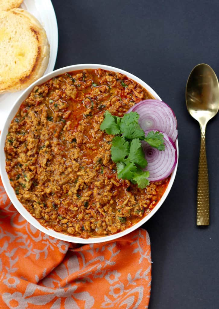 serving bowl with chicken kheema , garnished with cilantro and red onions.  Toasted roll on the side.