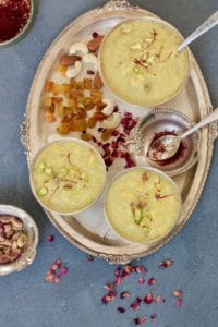 Rice Pudding served in 3 silver bowls in a silver tray with raisins, nuts and saffron in bowls